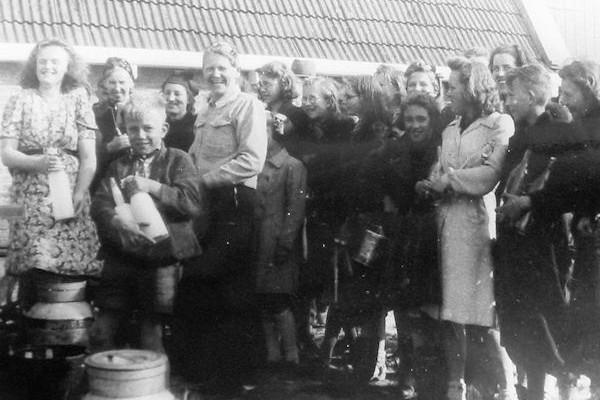 Naarmate de oorlog vorderde werd het ook steeds moeilijker om aan melk te komen. Wie melk wilde moest 'de boer op'. Hier poseert een groepje Harlinger vrouwen bij een boerderij even buiten de stad.  Foto: Collectie mevr. G. de Jong